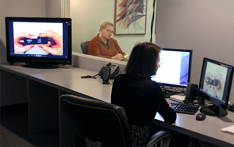 A notetaker watching a usability test session through one-way glass at a UserWorks lab